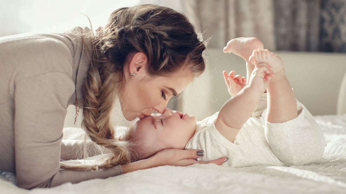 A mom kissing her baby on the forehead.