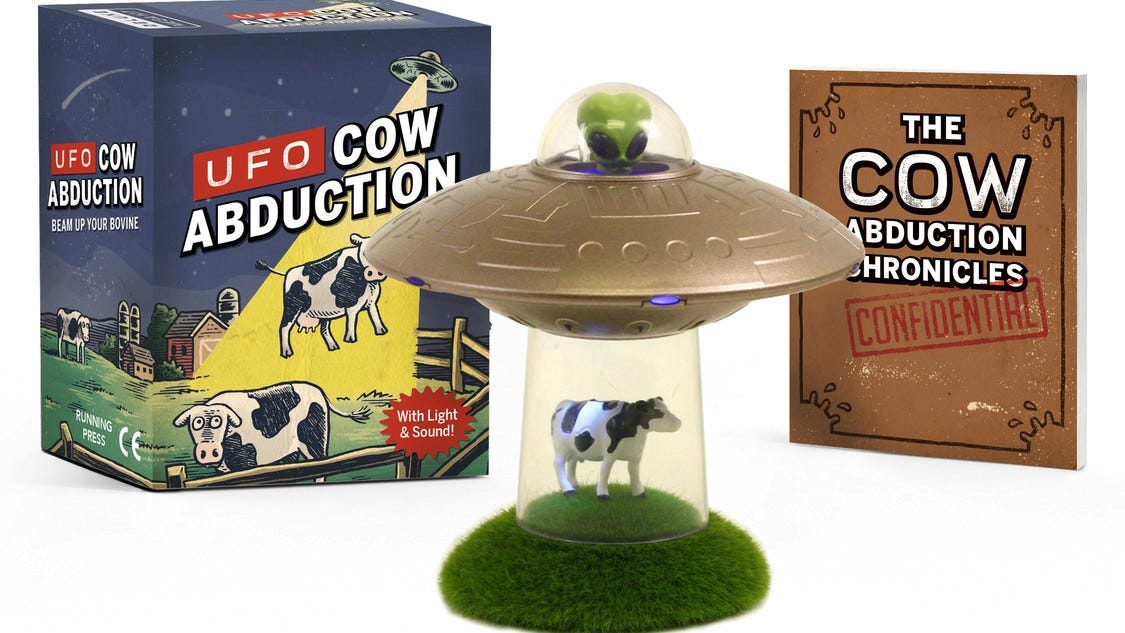 Cute mini light featuring a cow being abducted by a UFO and a book on cow abductions.