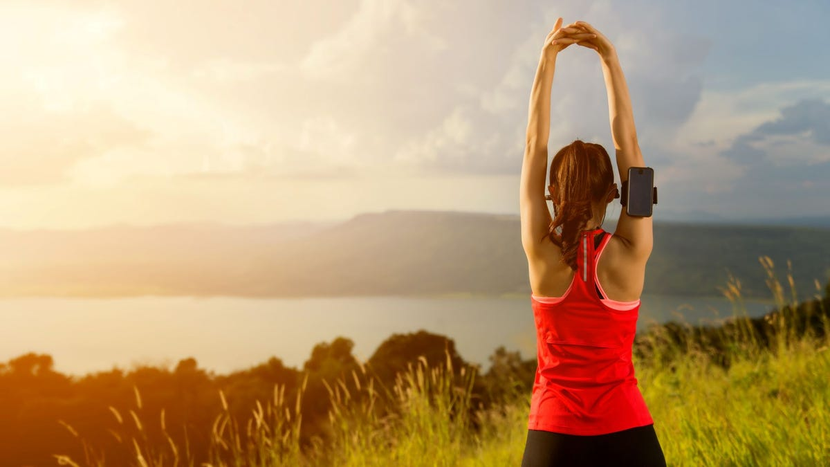 A woman doing yoga near a lake in the morning.