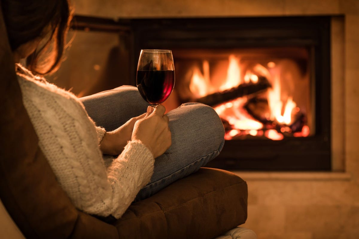 A woman relaxing with a glass of wine in front of a fireplace.