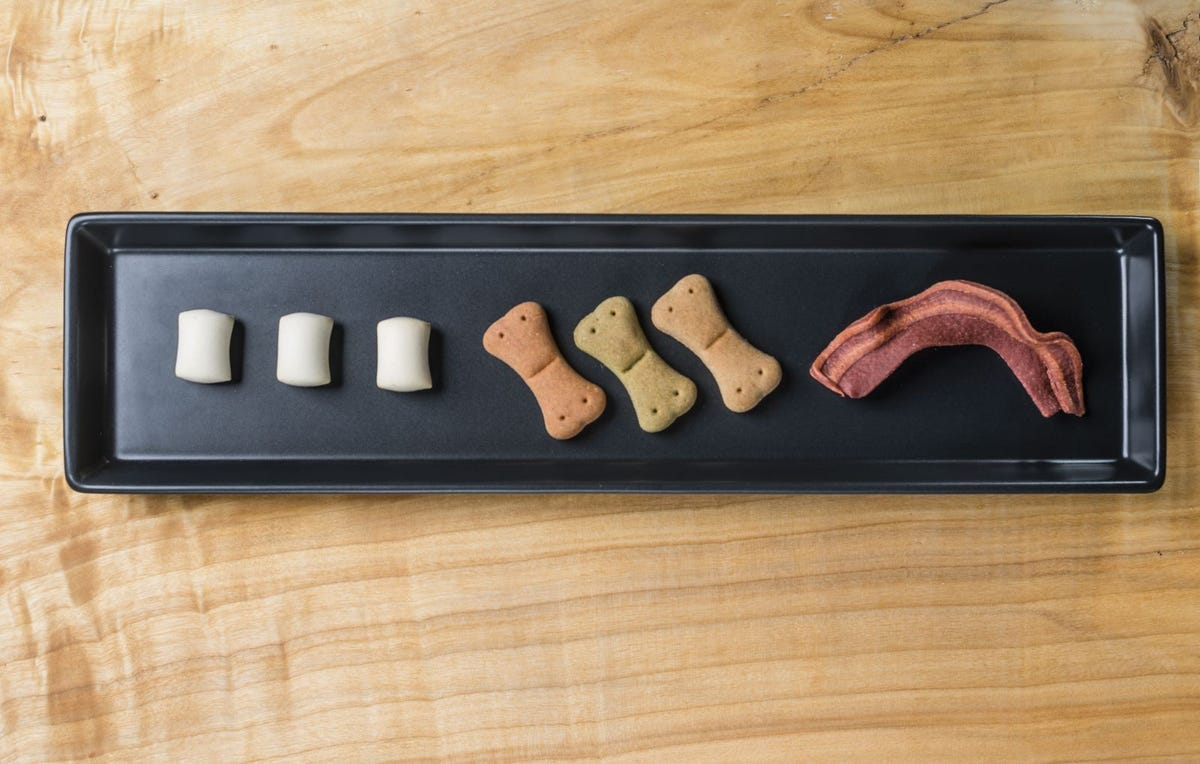 A dogcuterie tray with three different dog treats.