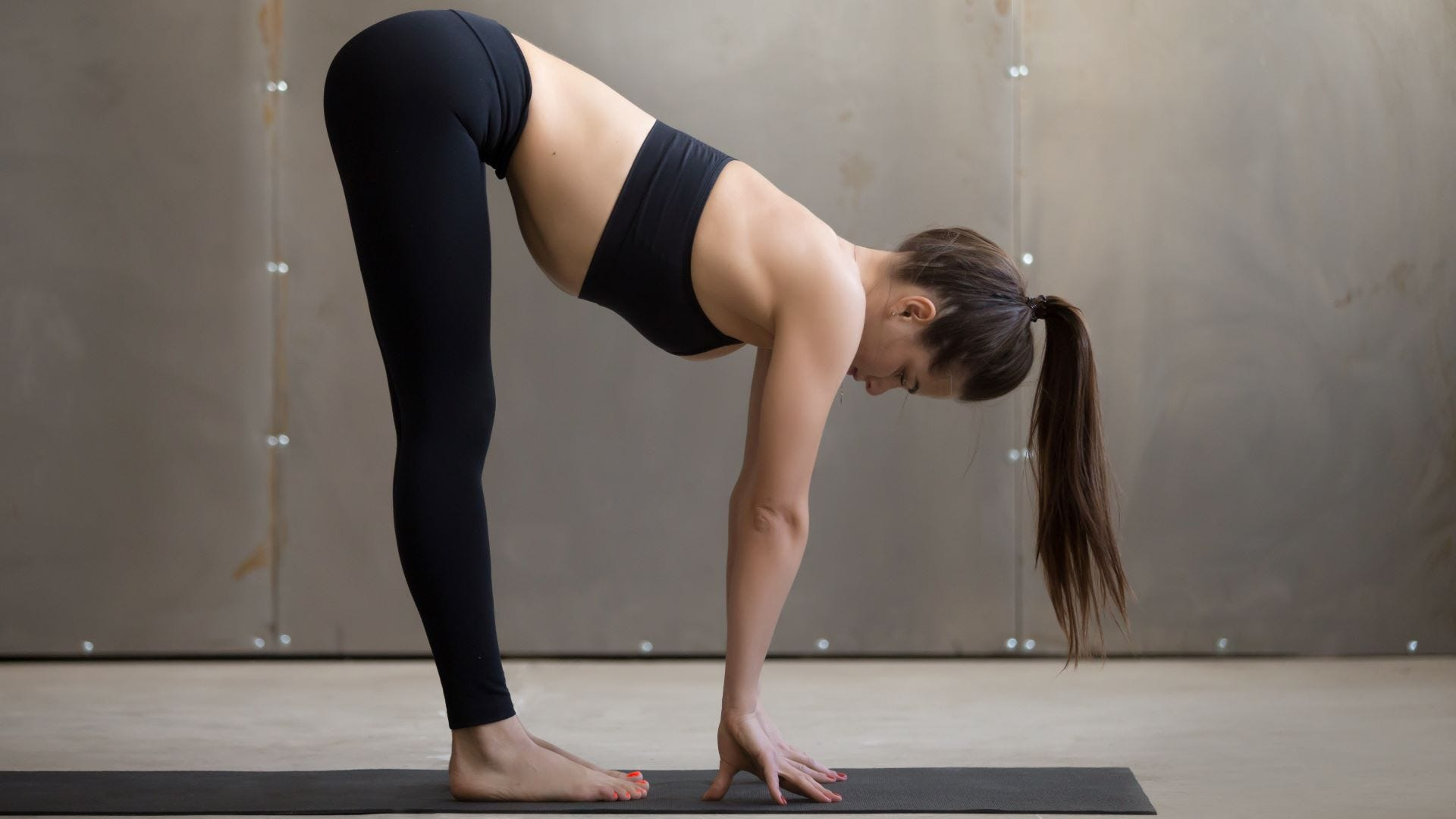 A woman doing a standing forward fold on a yoga mat.