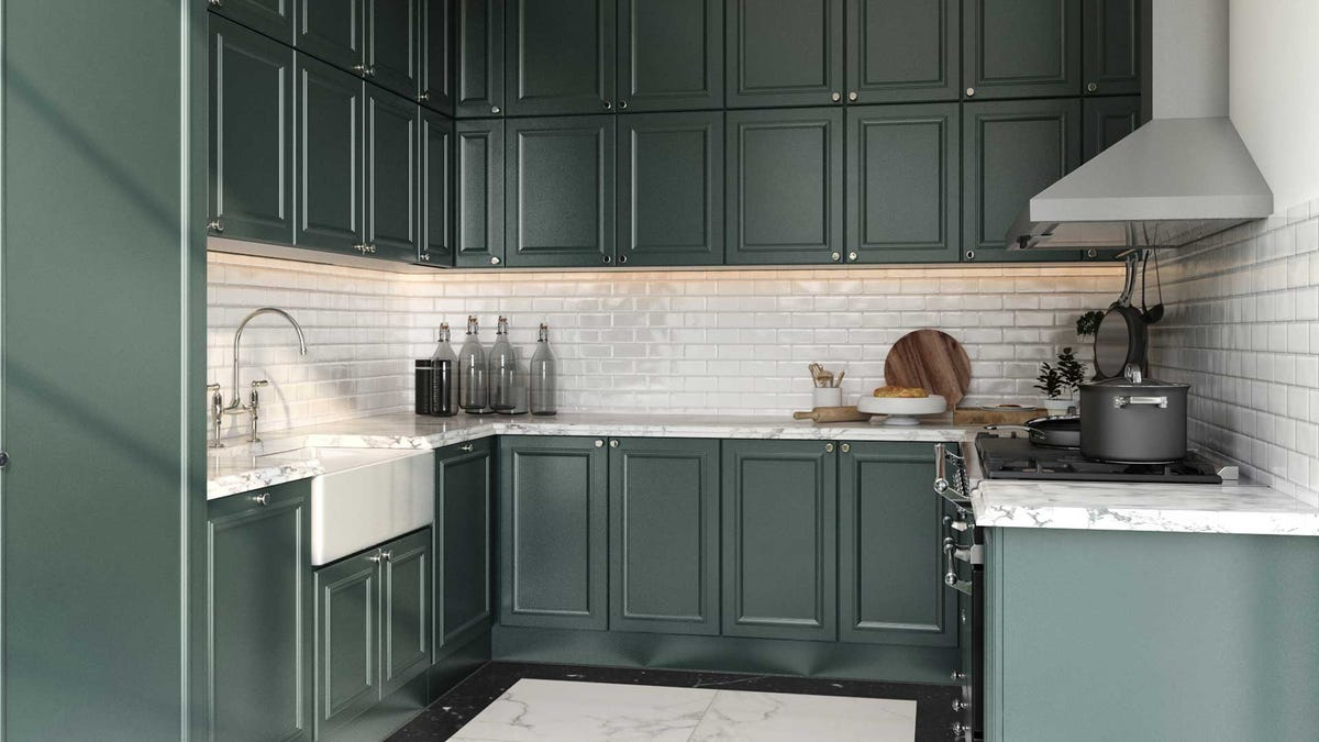 A kitchen with rich green cabinets and a white tile backsplash.