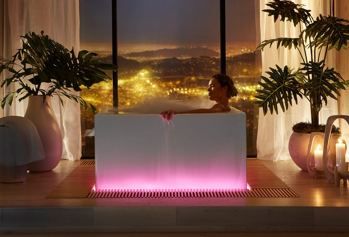 A woman in a Kohler infinity tub with hot pink ambient lighting.