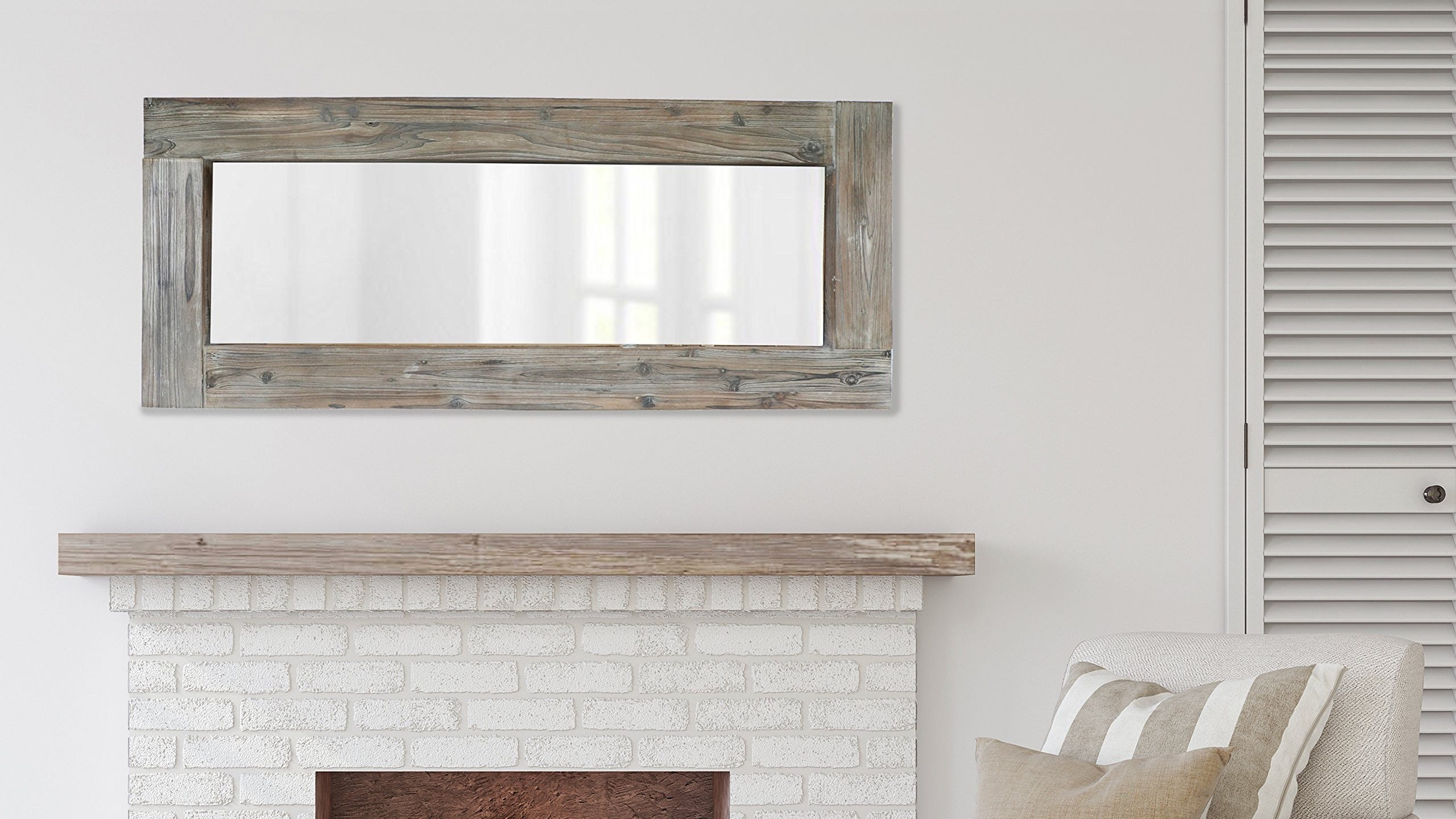 A mirror in a wooden frame hanging above a fireplace.
