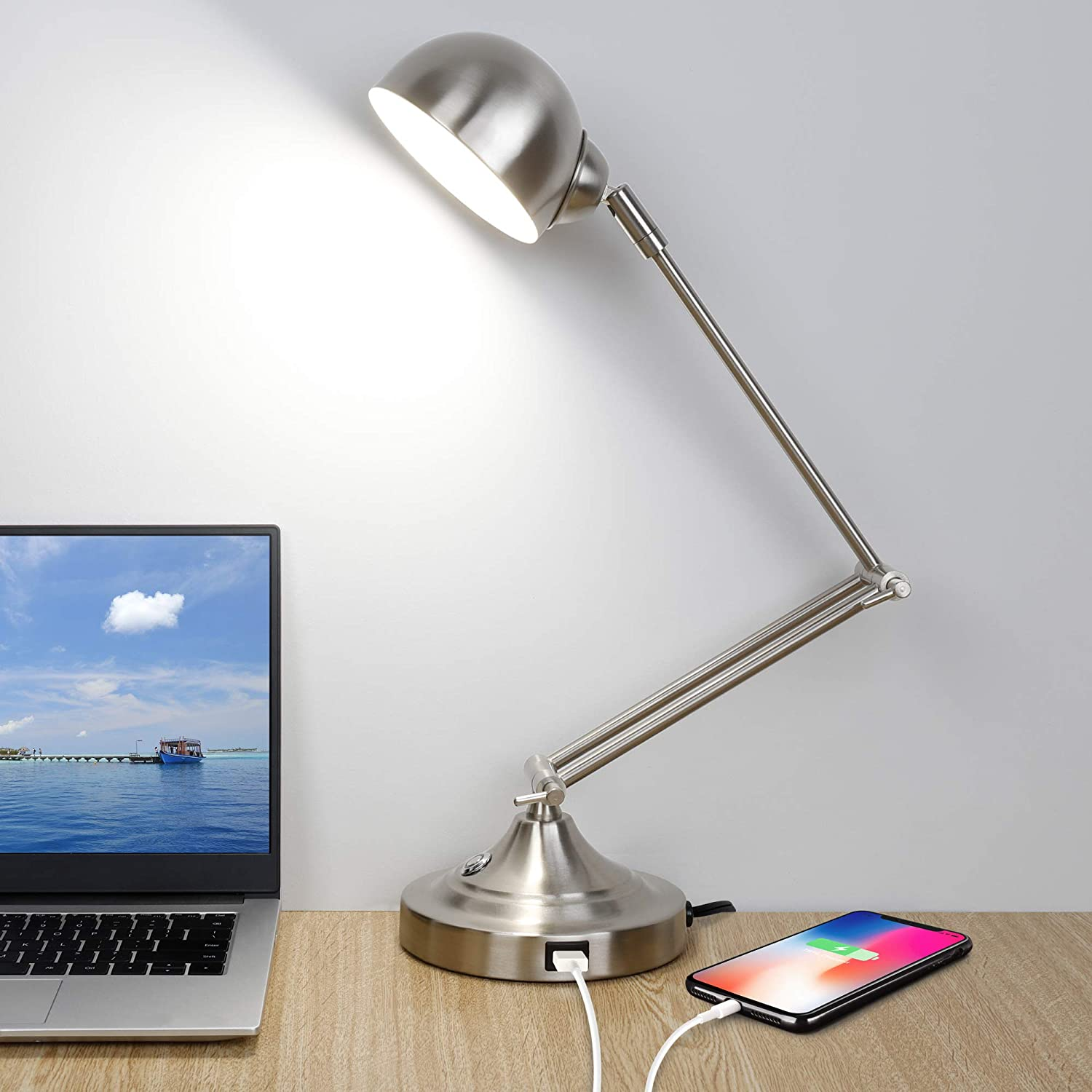 Silver lamp with bent neck sitting on a desk with a phone plugged in