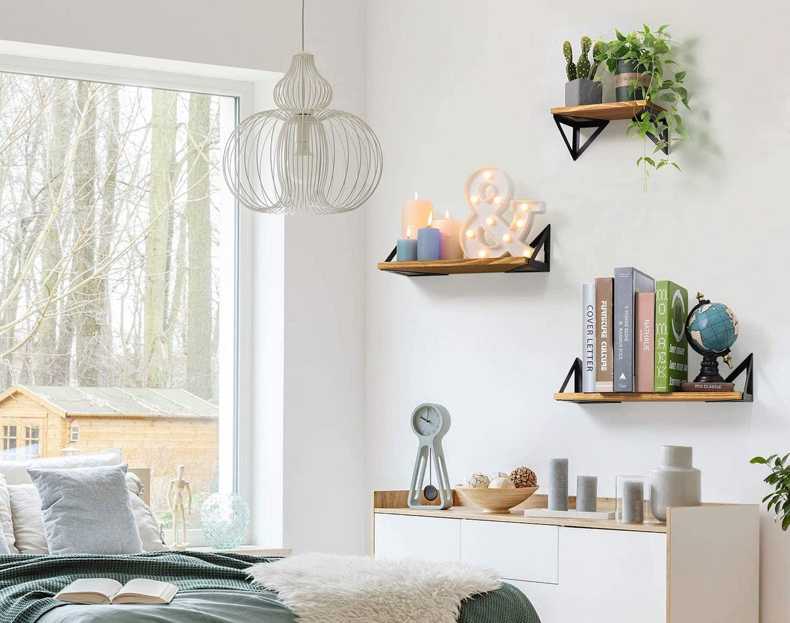 Floating shelves on a white wall, holding books, candles, and plants