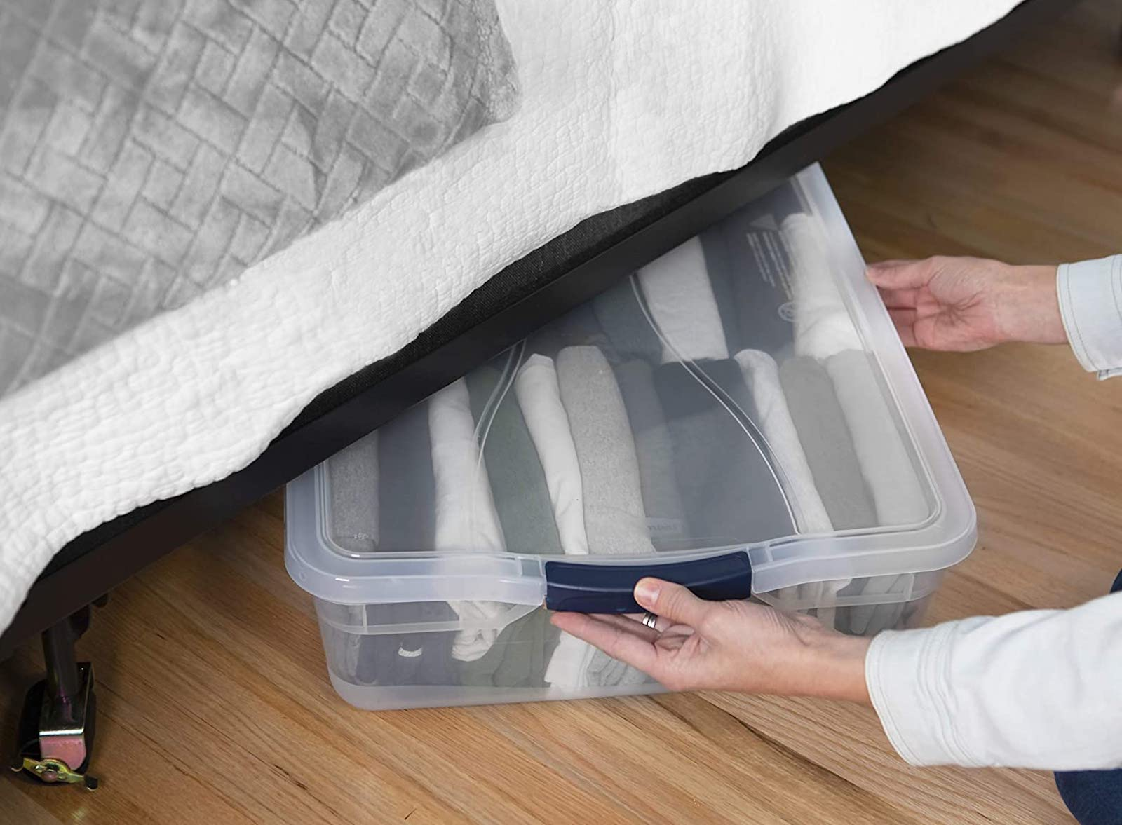Flat storage tub partially visible under a bed
