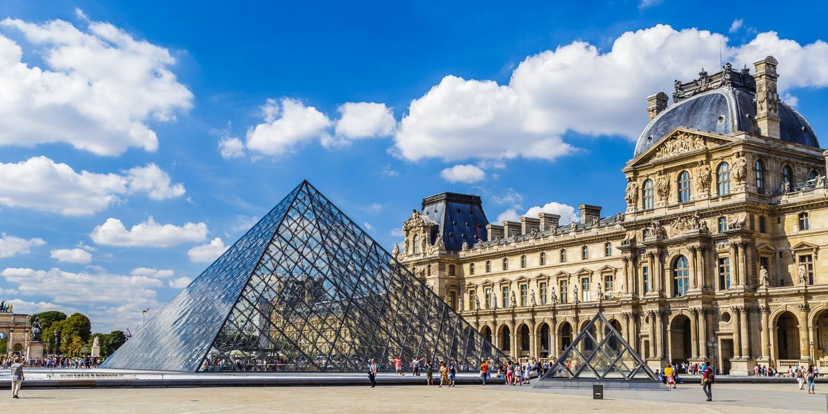 The glass pyramid and front of the Louvre Museum.