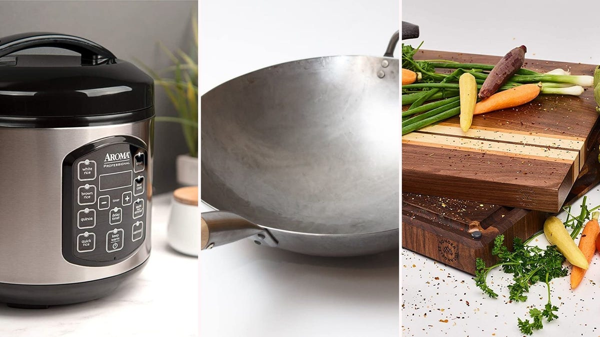 A rice cooker, a silver wok, and a wooden cutting board with veggies on top
