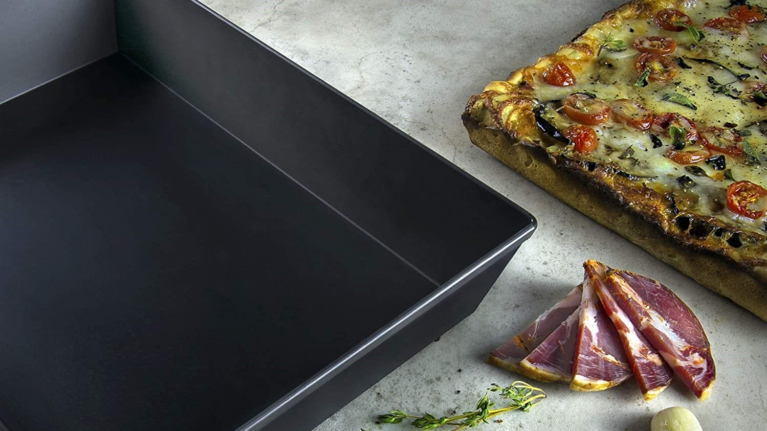 Detroit-style pizza pan next to a finished pizza and some random toppings.