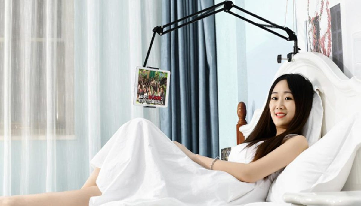 woman with a bedside device holder holding her tablet so that she can watch something on it with her hands free