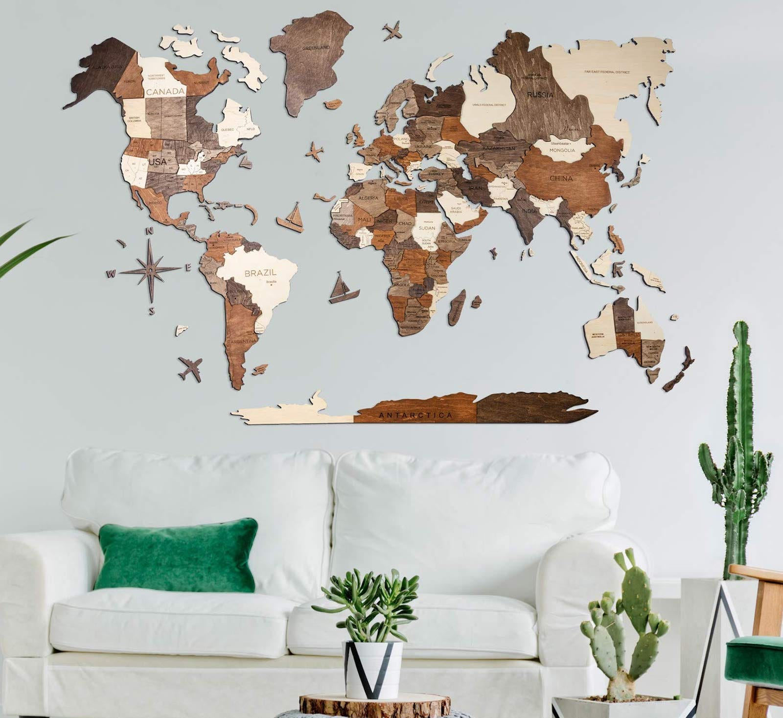 A 3D wooden world map on a gray wall above a white couch