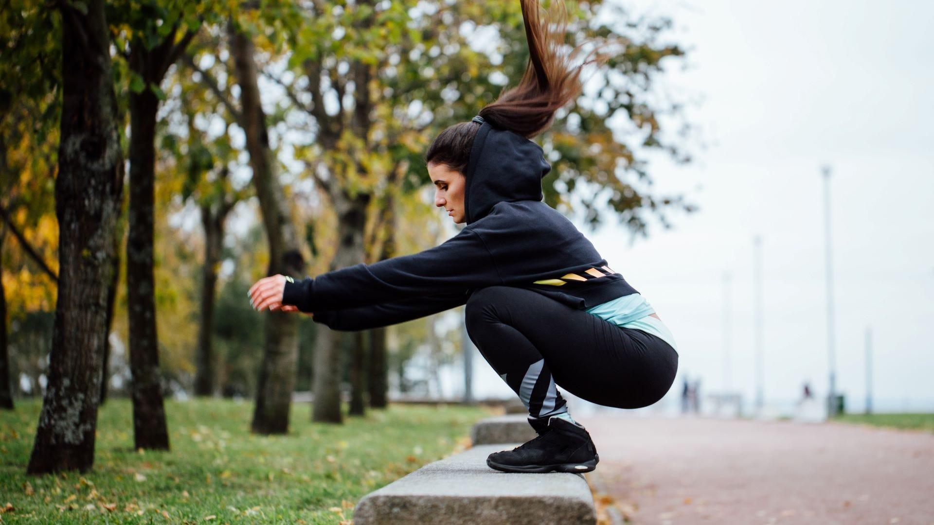 A woman doing a squat on a park bench.