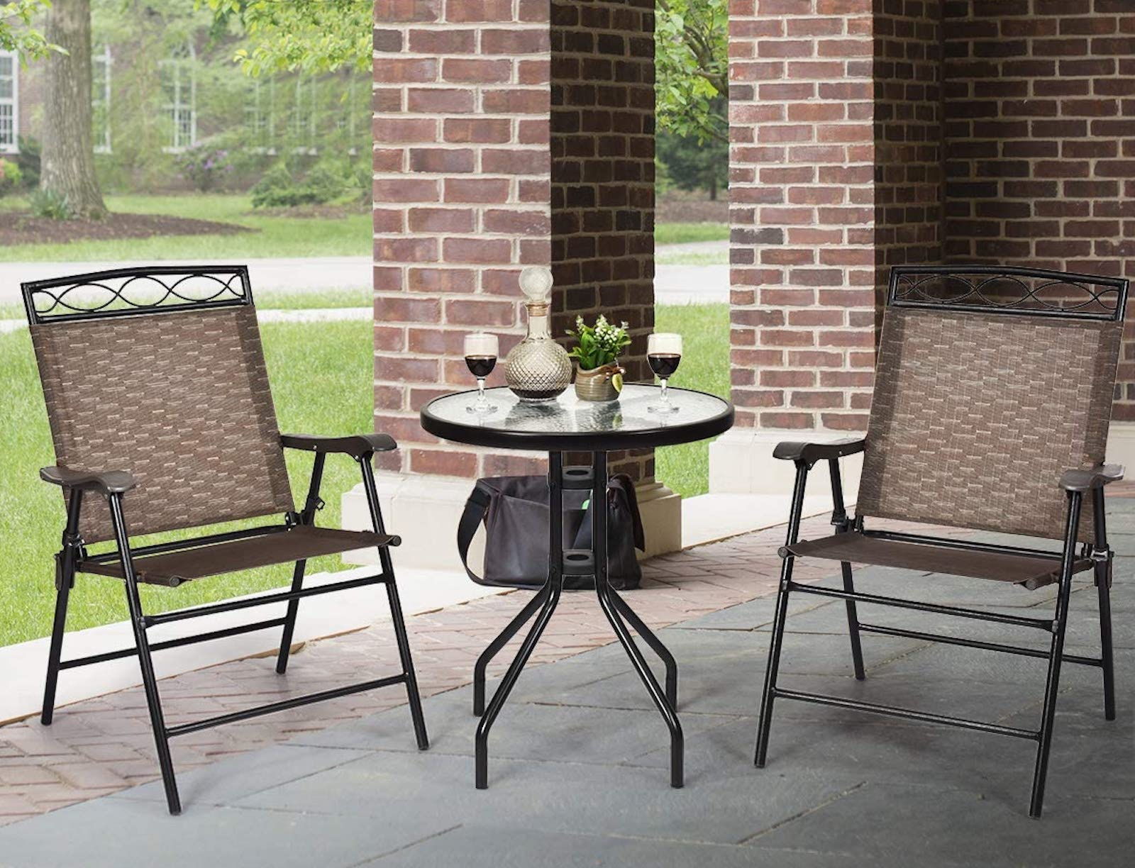 Two patio chairs on either side of a round, glass-top bistro table on a stone patio
