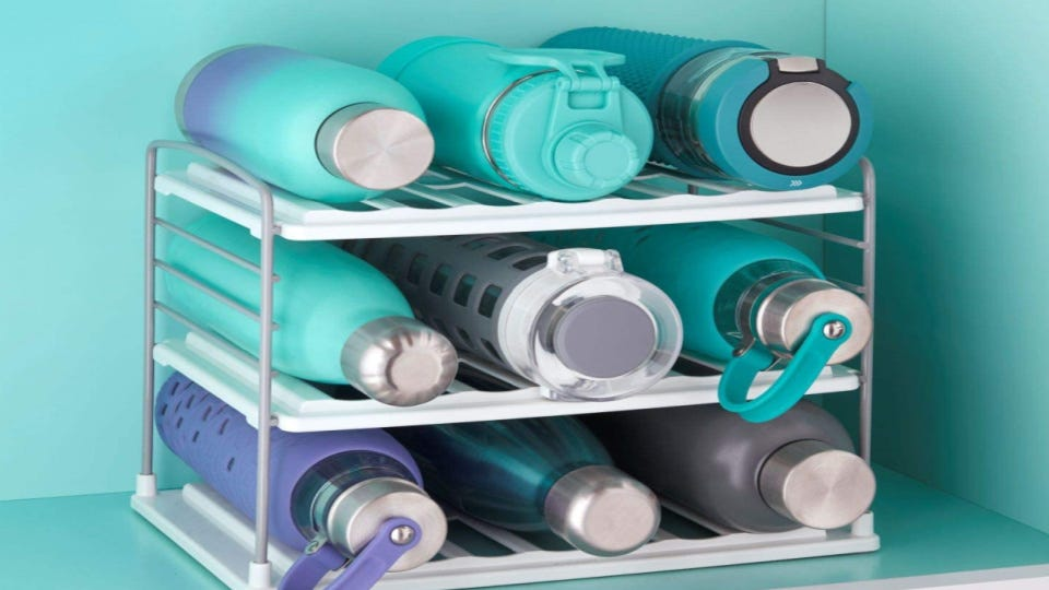 Nine reusable water bottles stacked neatly on an organizer rack.
