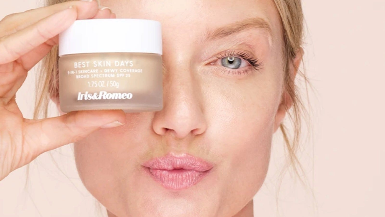 woman holding iris & romeo foundation in front of face