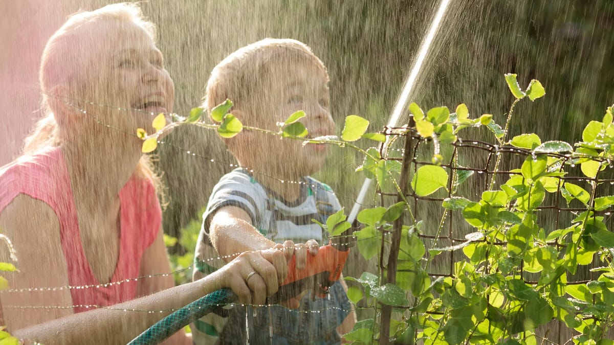 A woman and young boy watering a garden with a hose.