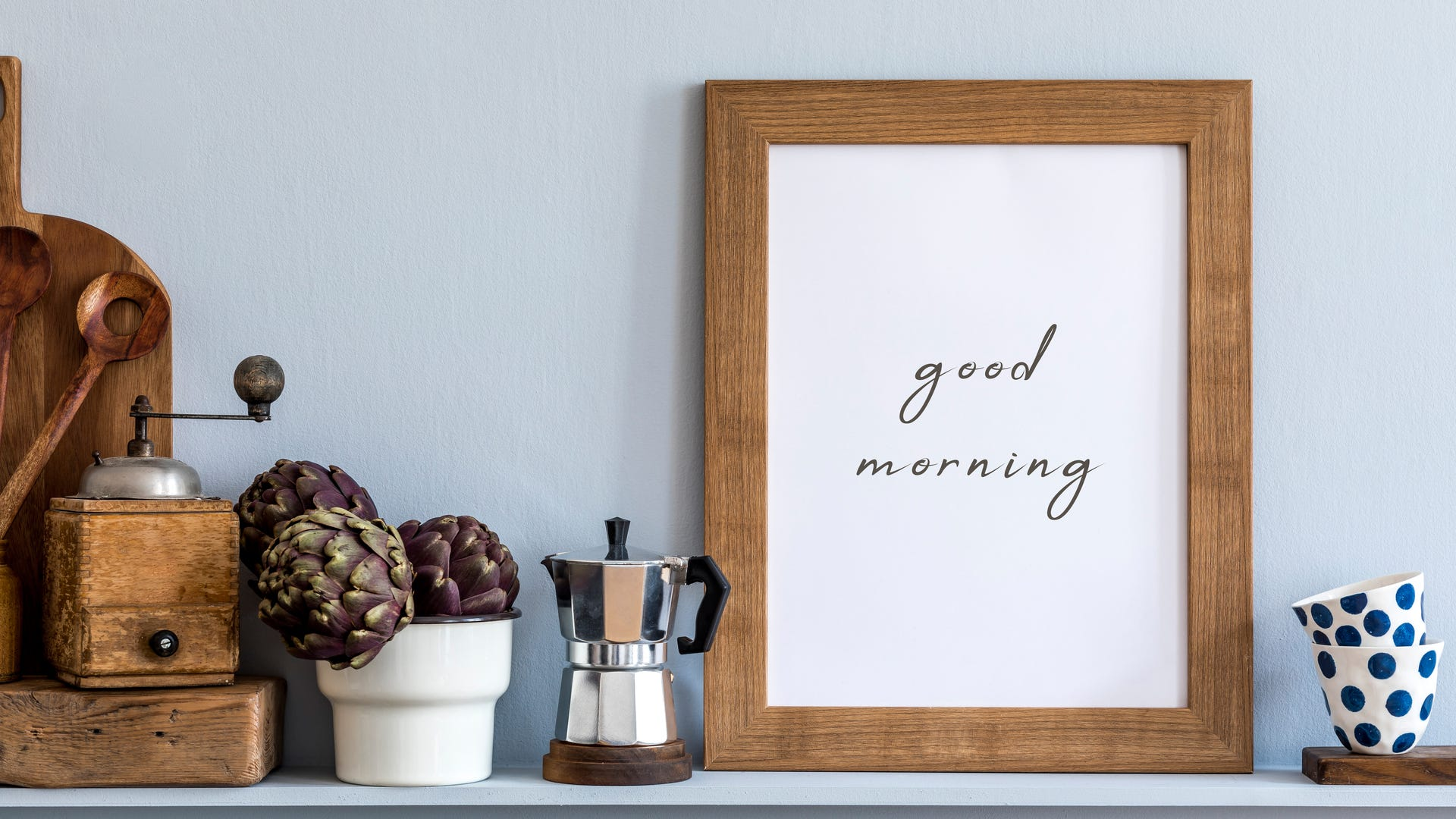 """A wooden frame around a sign that says """"Good Morning"""" next to a coffee maker."""