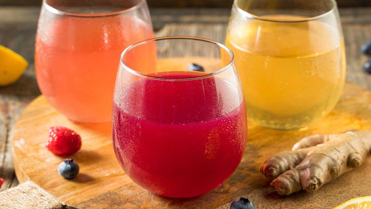 Alcoholic kombucha in stemless wine glasses on a wood cutting board.