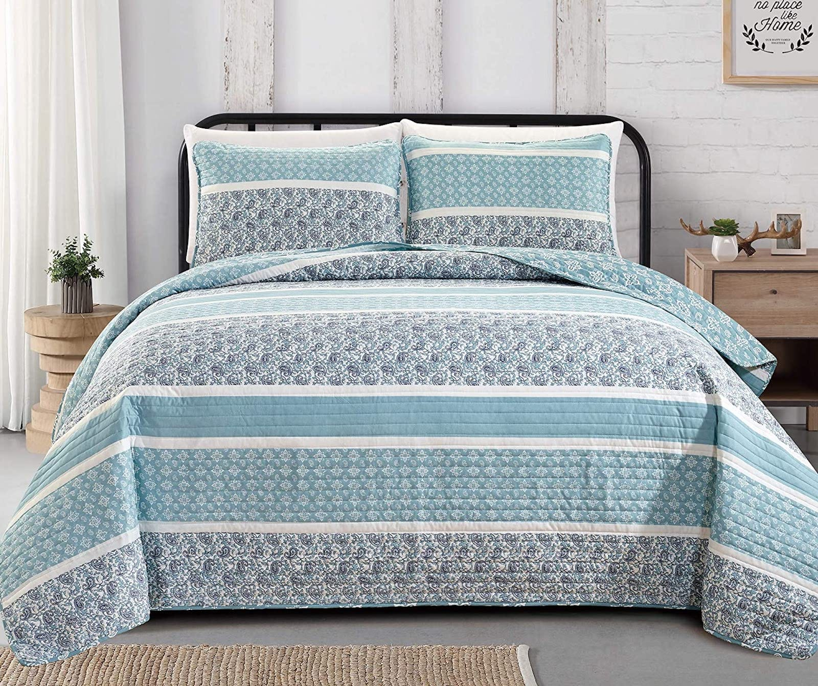 Bed with a blue striped/patterned quilt and two pillows