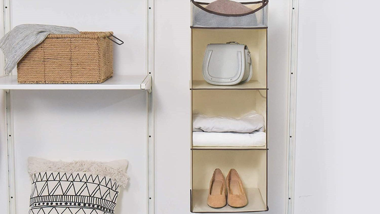 The StorageWorks hanging closet organizer with a bag, blanket, and pair of shoes stored on its shelves.