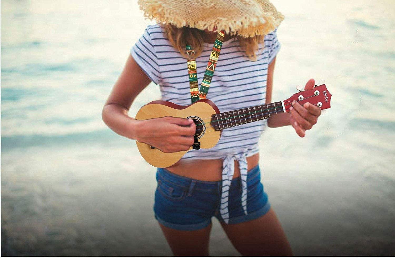 A woman playing a ukulele on the beach.
