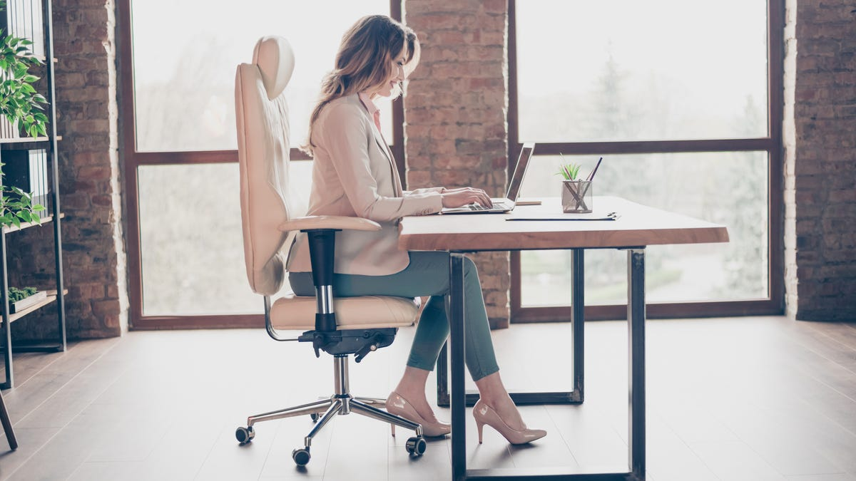 A woman sits at her desk in an office chair and works on her laptop.