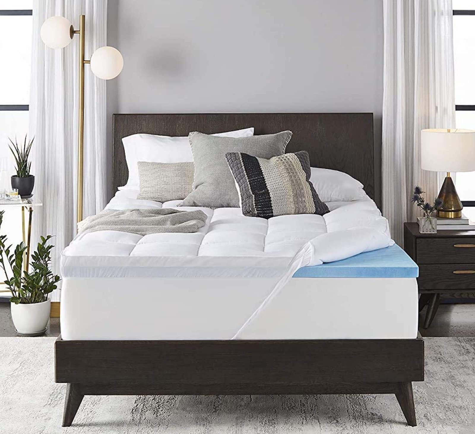 A bed with the white top pulled back to reveal a blue foam mattress pad