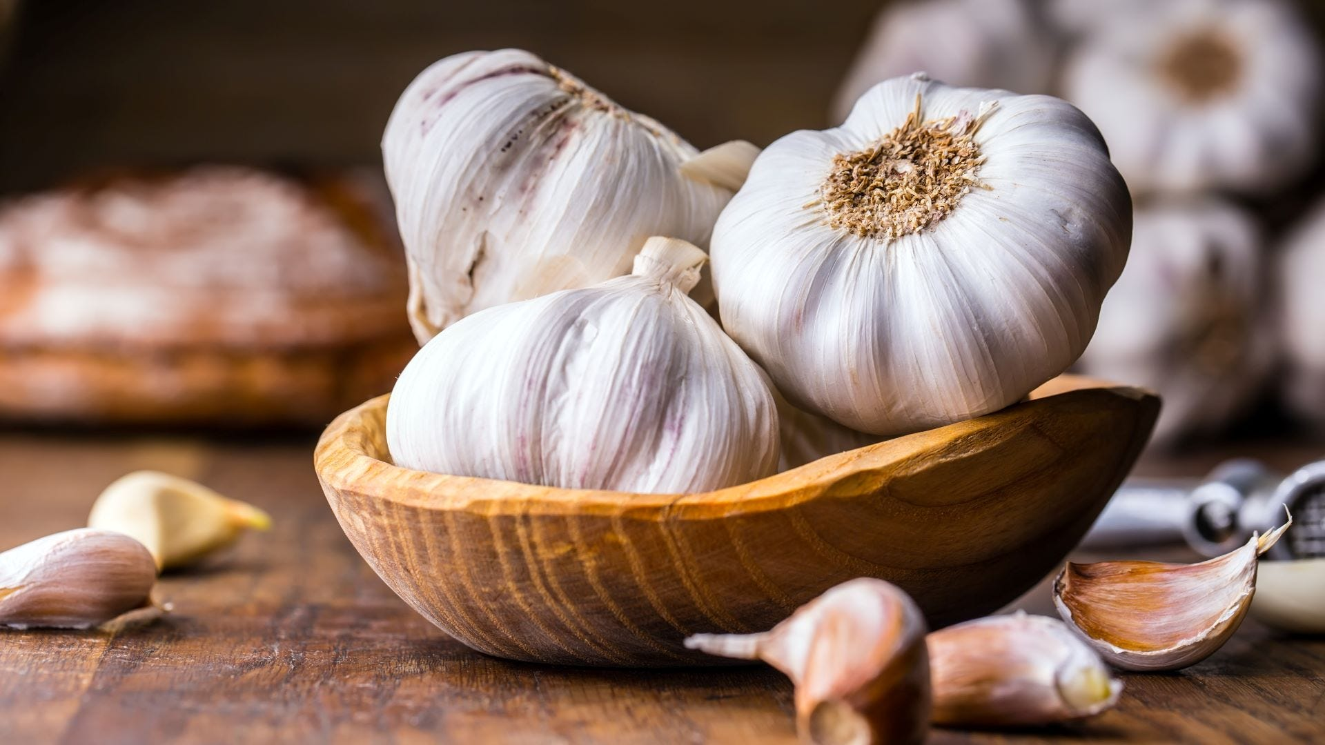 A bowl holding three garlic cloves.