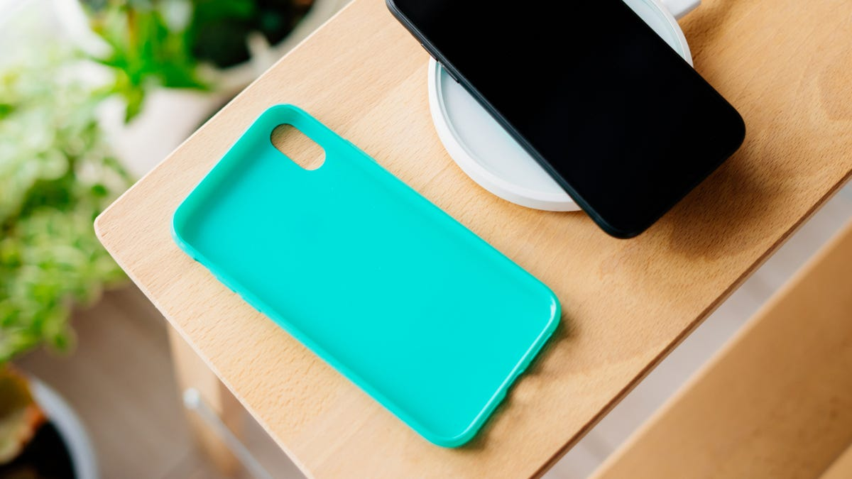 A black smartphone with a mint silicone case is charged from a wireless charger.