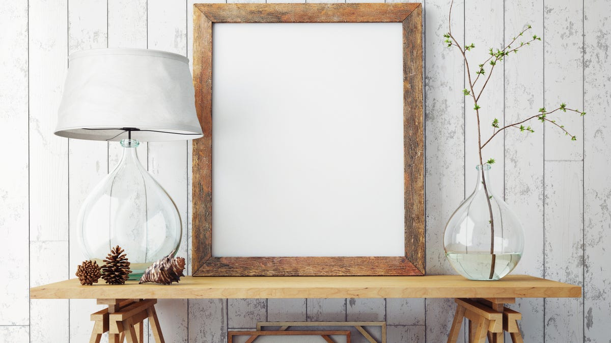 A wooden frame rests on a wooden table next to a lamp and vase.