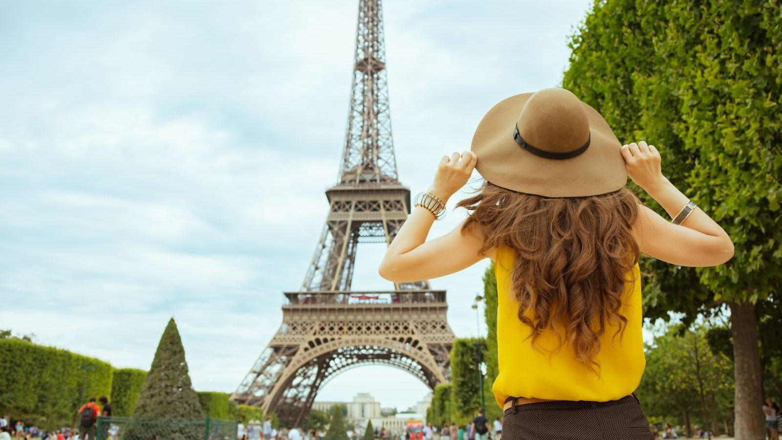 A young woman looking up at the Eiffel Tower.