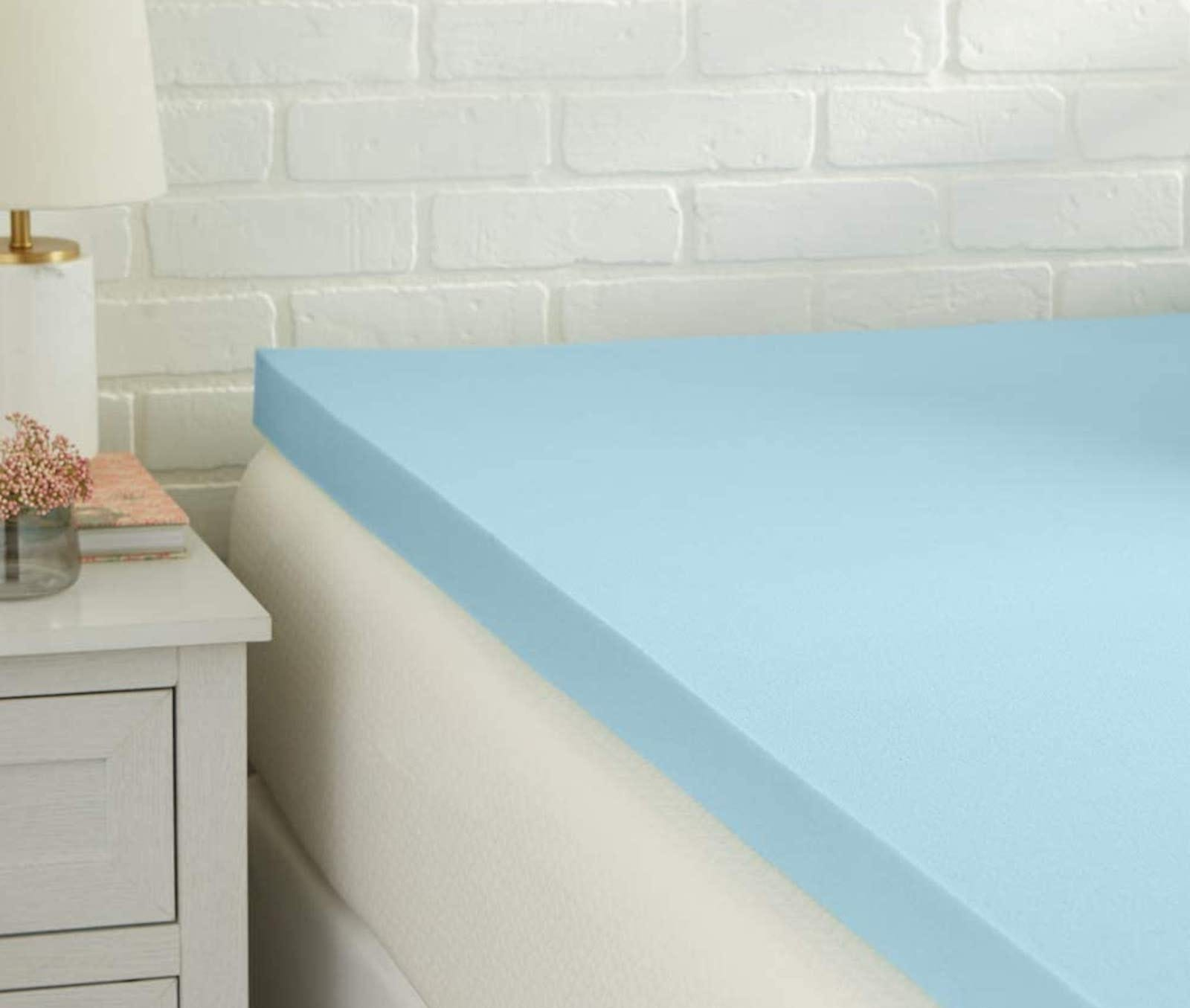 The corner of a blue foam mattress topper atop a white mattress