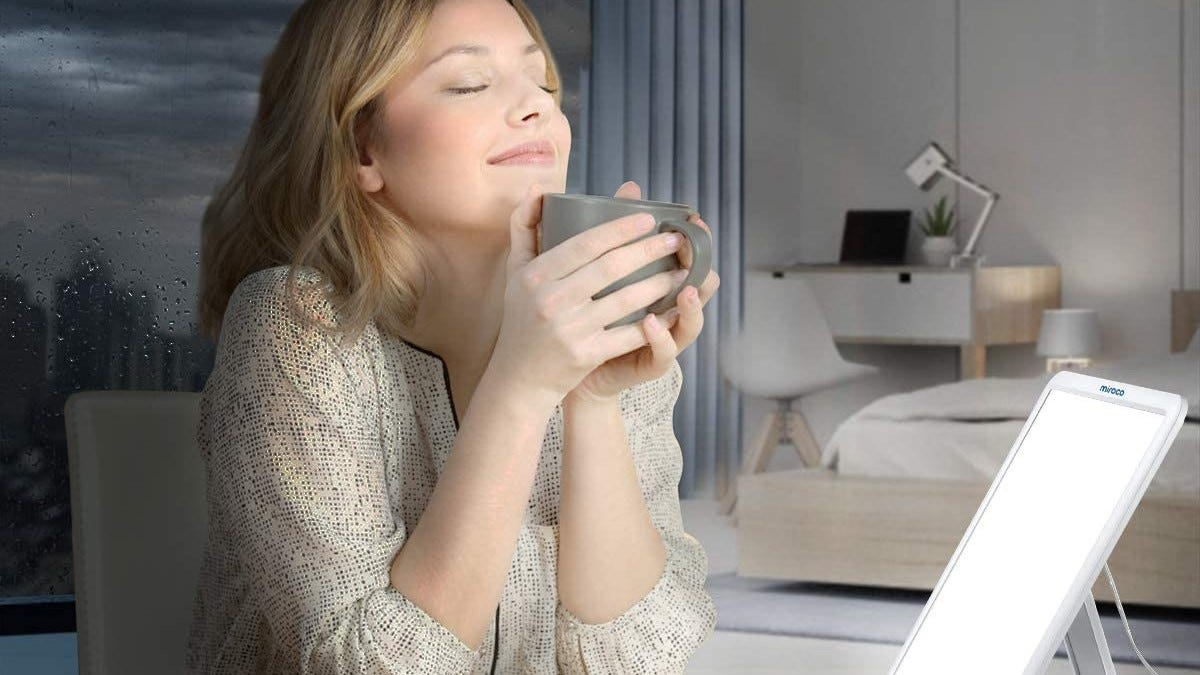 A woman holding a mug in front of the Miroco Light Therapy Lamp.