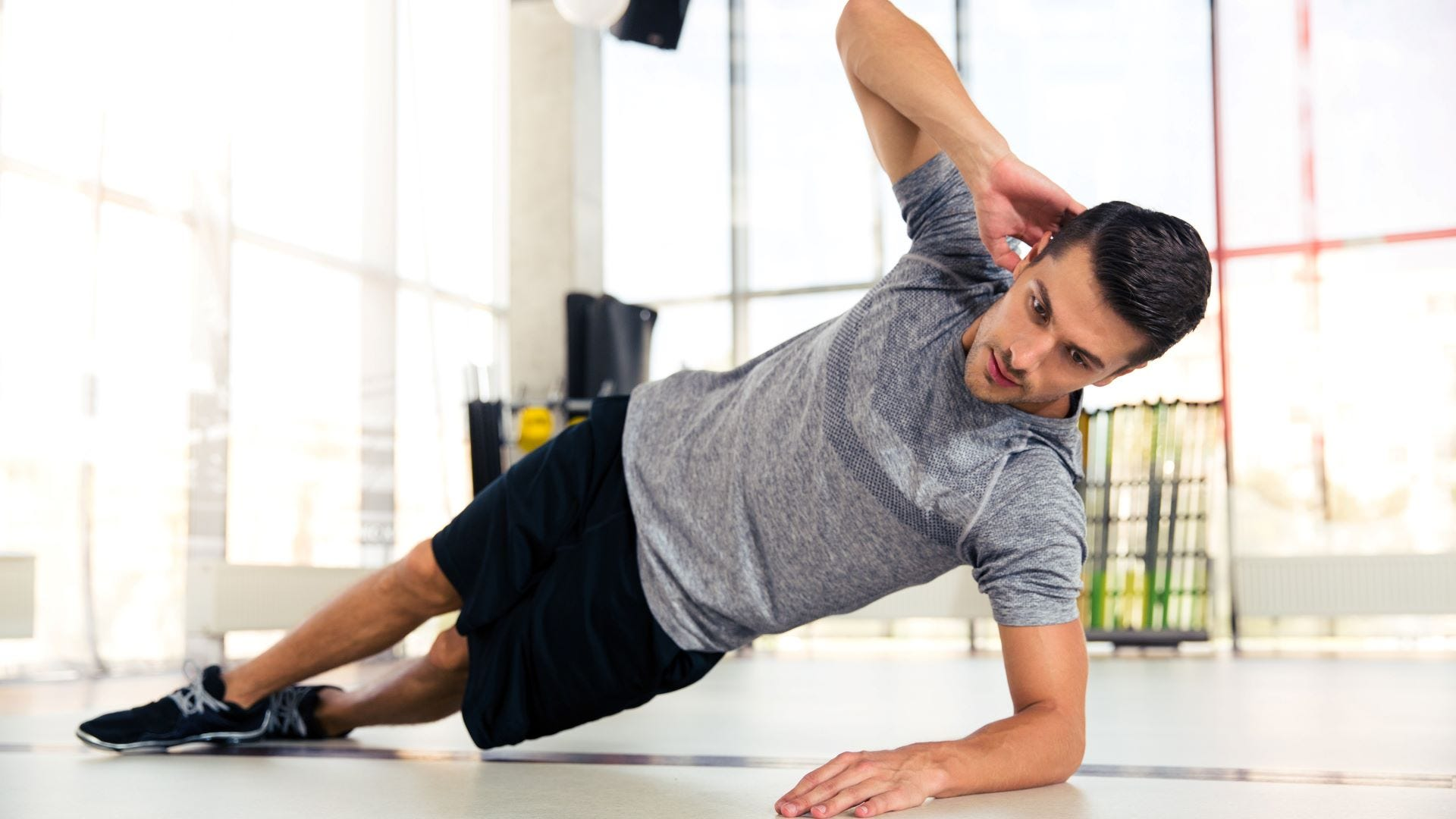 A man doing the side plank yoga pose.