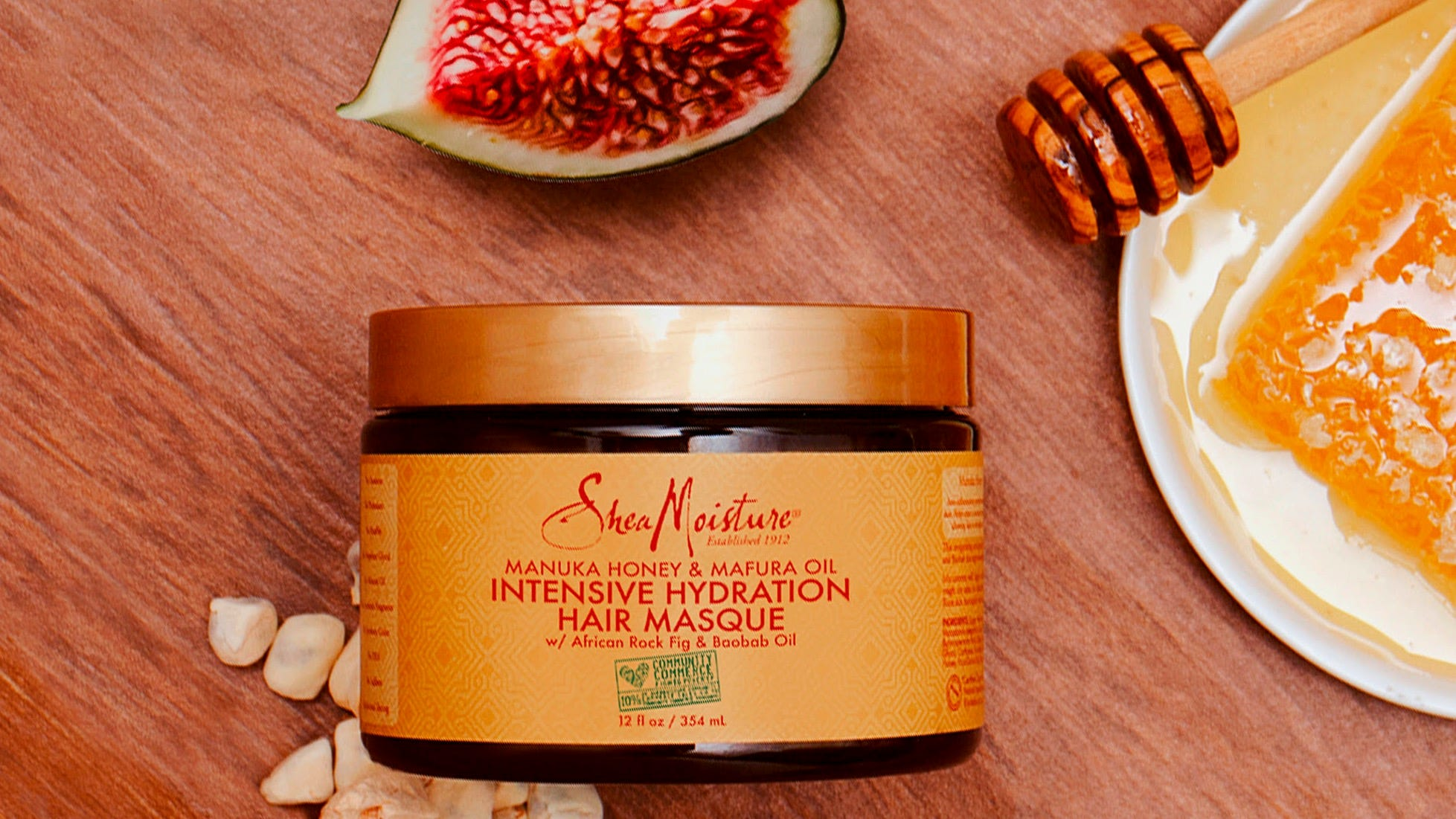 A jar of Shea Moisture Intensive Hydration Hair Masque on a table next to some sliced fruit and honey.