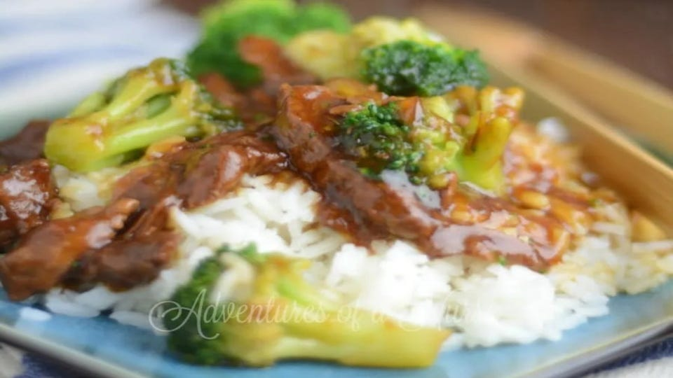 White rice topped with pressure cooker beef and broccoli.