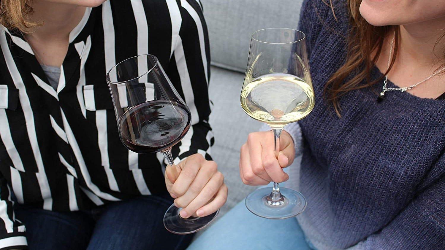 Two women holding Gabriel-Glas crystal wine glasses.