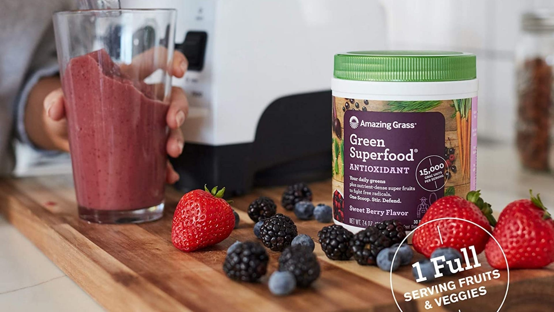Someone setting a red smoothie on a counter next to a container of Amazing Grass, surrounded by raspberries, blueberries, and strawberries.