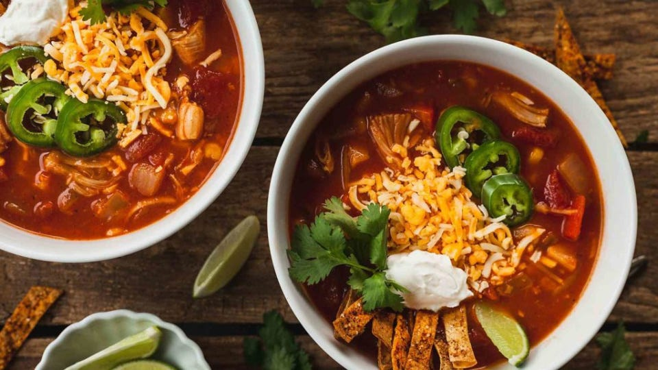 Two bowls of jackfruit tortilla soup, topped with slice jalapenos, shredded cheese, tortilla strips and a dollop of sour cream, with fresh lime wedges on the side.