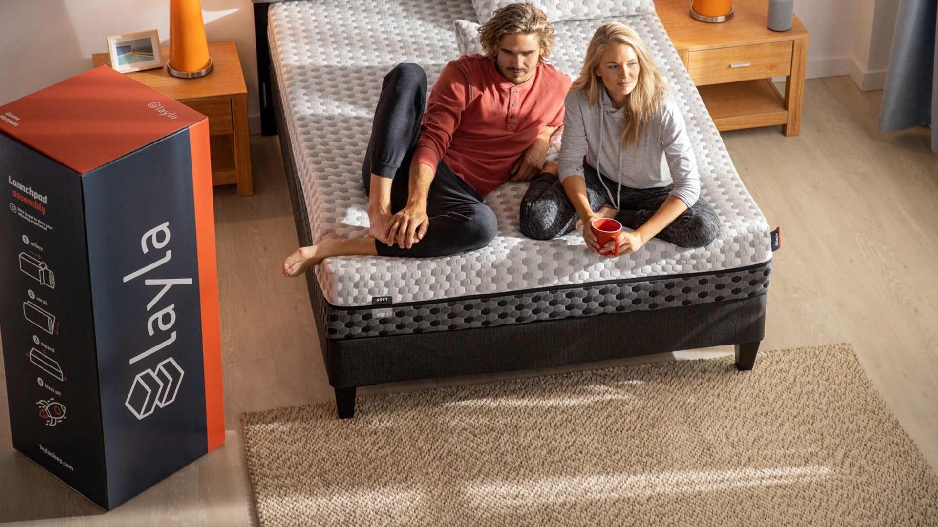 A couple sitting on a newly unpacked Layla mattress.