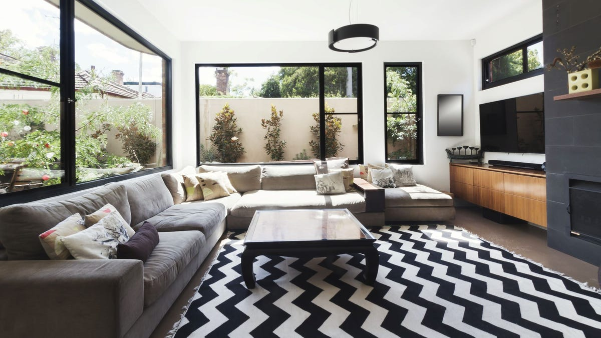 A living room with wood and gray tile accents and a chevron black and white rug