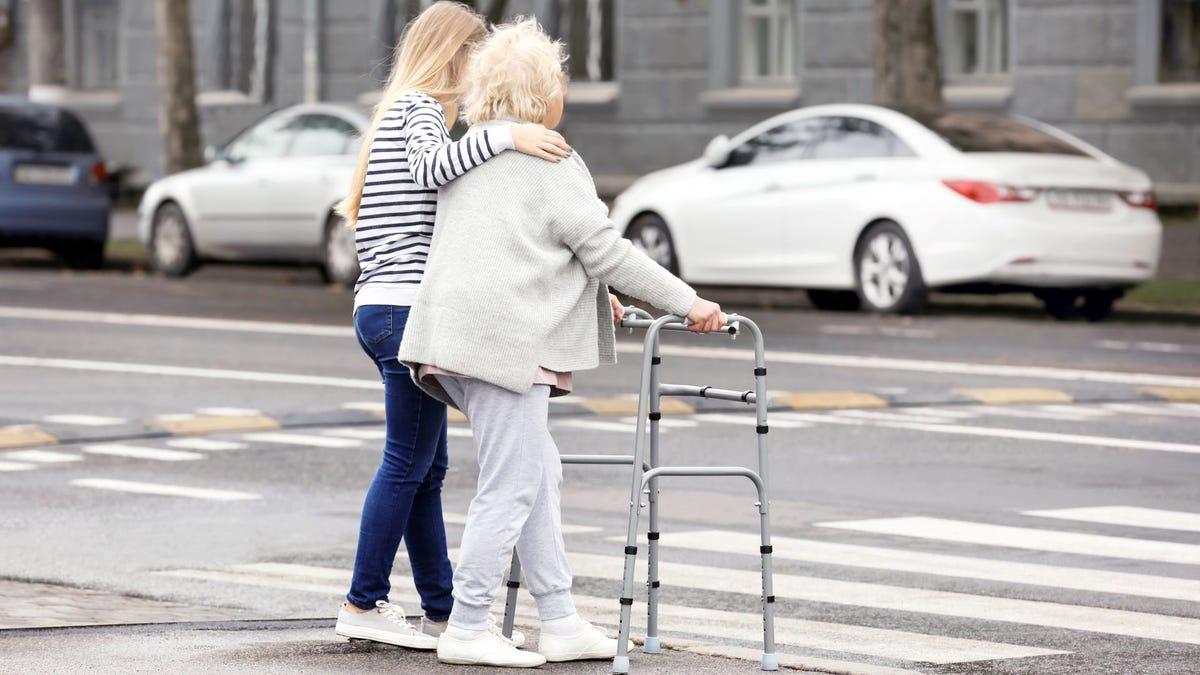 A young woman helping an elderly woman with a walker cross a city street.