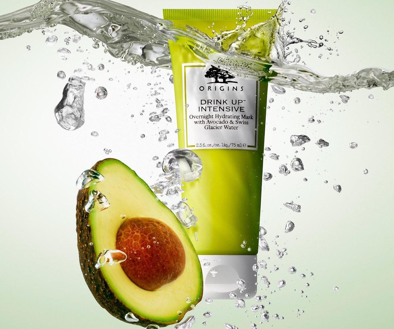 A green tube of mask cream, next to an avocado half and a splash of water