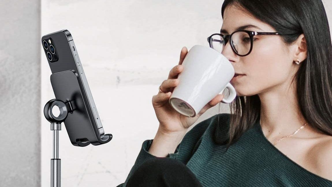 A woman drink from a mug while watching her phone on a Lisen media stand.