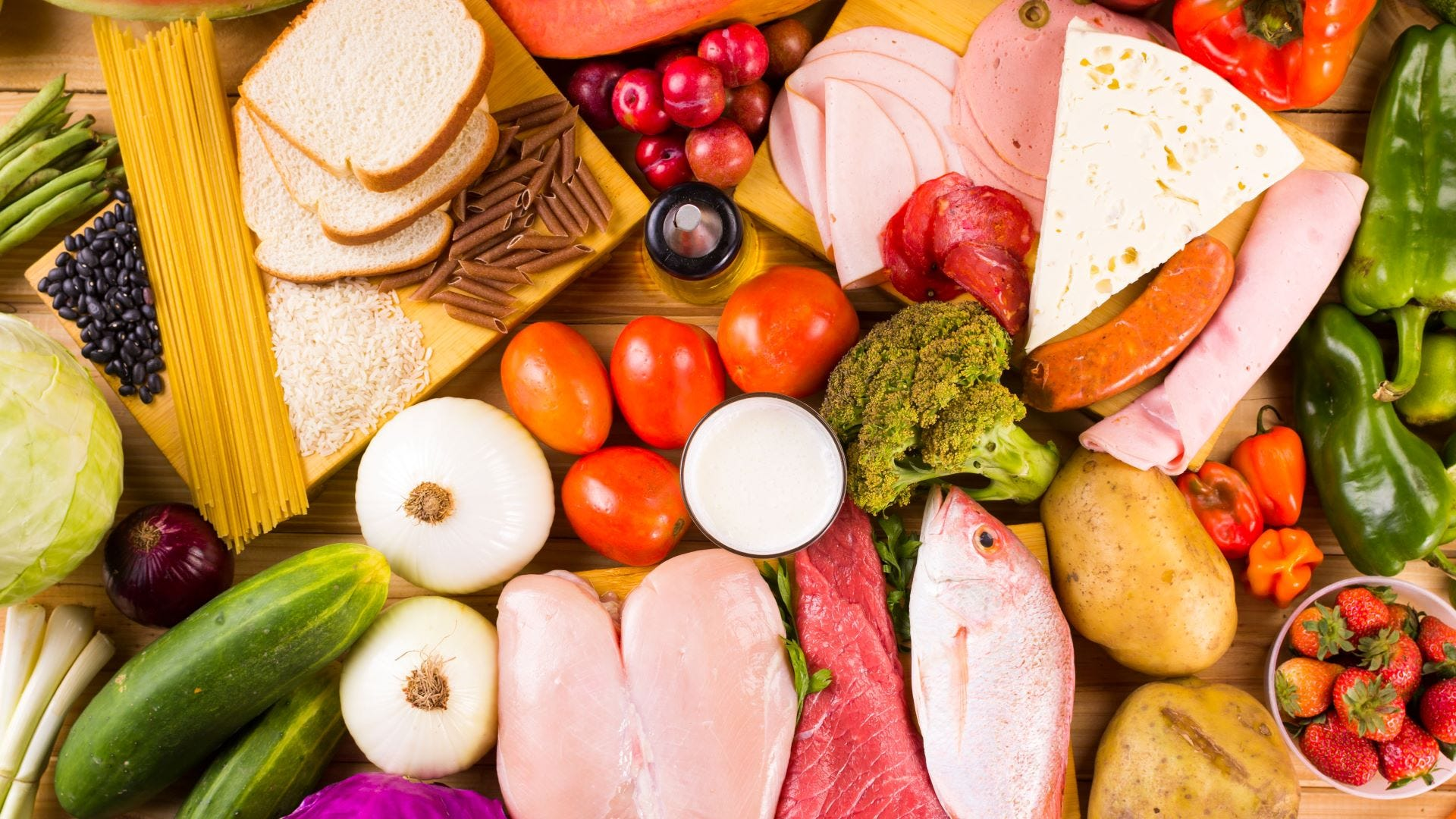 A pile of veggies, meats, breads, fruits, and berries on cutting boards.