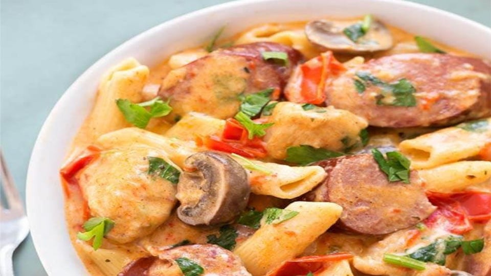 A bowl full of Cajun pasta with mushrooms and andouille sausage.