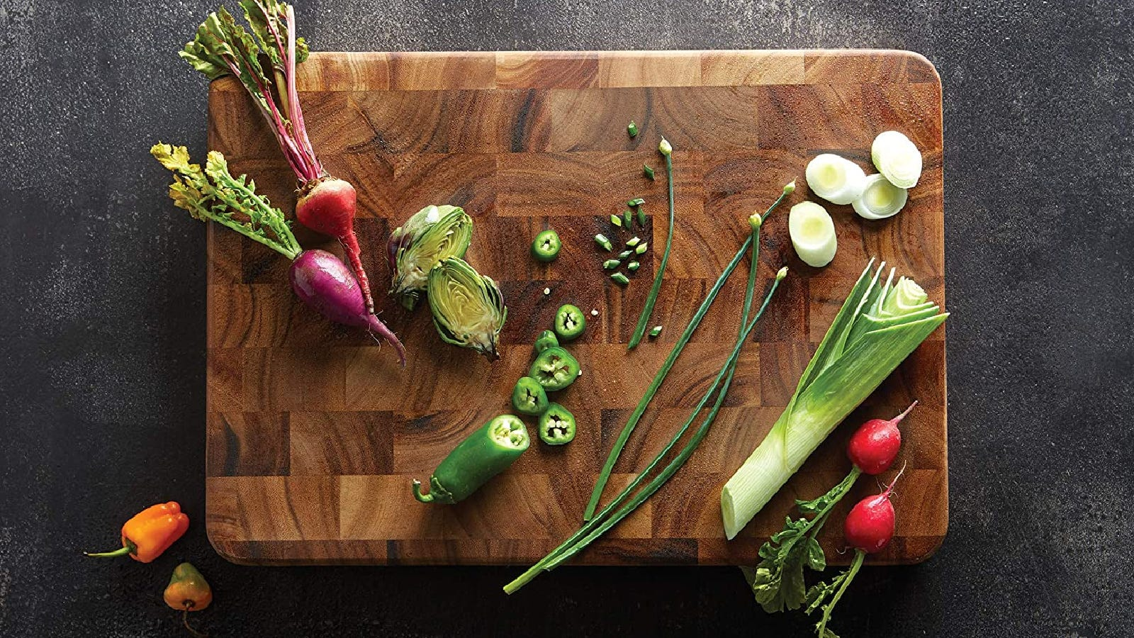 An edge grain woodent cutting board made from acacia wood by Ironwood Gourmet with various vegetables presented on top.