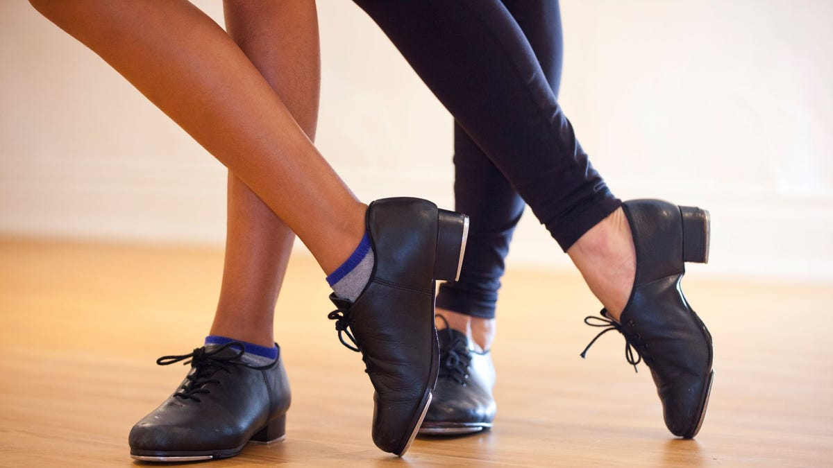 Two people wearing tap shoes with one leg crossed over the other.